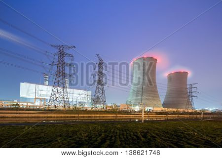cooling towers with red smoke and pylons in modern power plant at twilight