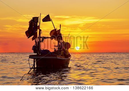 silhouette of fisherman boat with during sunset in Thailand