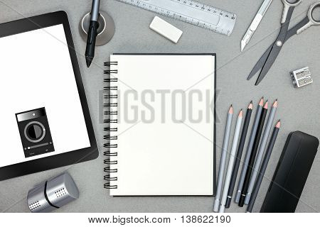 Notebook With Various Drawing Tools And Tablet With Stylus On Gray Background