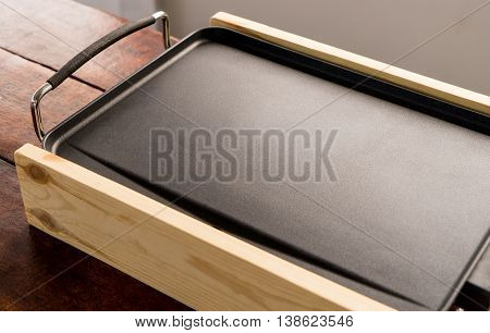 Empty Electrical cooking pan on wooden table. Small portable cooking pan with copy space.