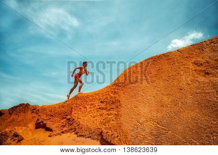 Young caucasian female runner running on a peak over the red mountains