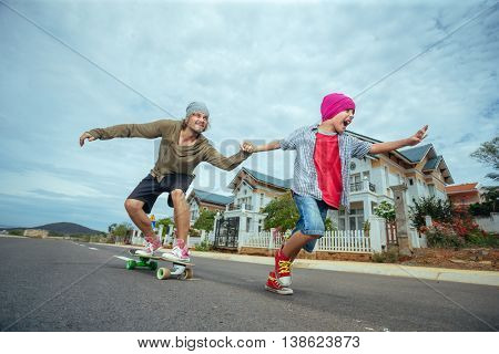 Father learning to ride skateboard as his son in the suburb street having fun