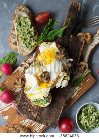 Tasty snack of open sandwich with fried egg, avocado and mushrooms on a wooden cutting board