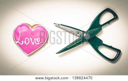 Scissors cutting a heart vintage sullen background. Heart breaking.