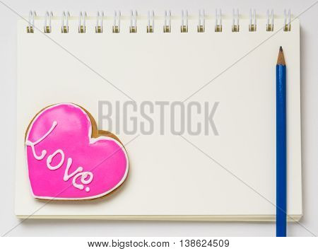 Love Diary Note book Blank book with pencil. Heart shaped Cookie on a blank diary page.