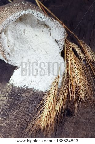 Still life with wheat and flour on wooden background. Wheat ears and flour sack on wooden board. Flour wheat closeup.
