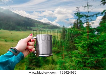 Travel metal cup in female hand with mountain is background. Cup of coffee or tea with beautiful view of mountains in background