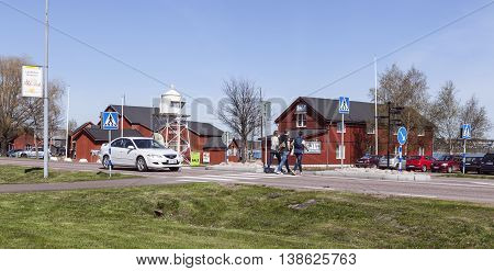 MARIEHAMN, ALAND ON MAY 07. View of a small town by the sea on May 07, 2016 in Mariehamn, Aland. Unidentified people cross the road in the sunny spring. Beacon and red buildings. Editorial use.