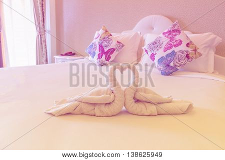 Pink bedroom with folded towel in swan shape on bed prepare for lover in resort Thailand