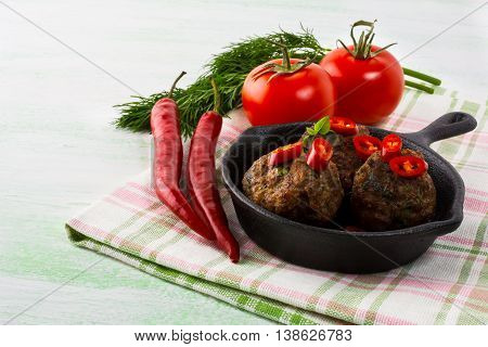 Grilled meatballs served with chili pepper slices in cast iron skillet. Grilled bbq meatloaf. Barbecue Meatballs.