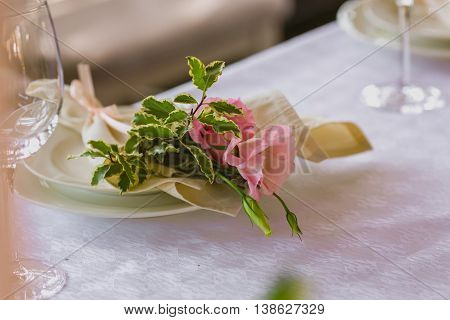 Spring table decoration with flowers. White plates and wineglasses