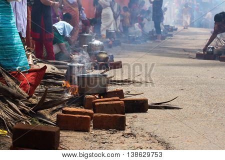 KOVALAM, KERALA, INDIA, April 1, 2015: Some women devotees participate in Pongala ceremony where boiled rice made in clay pots is offered to the god