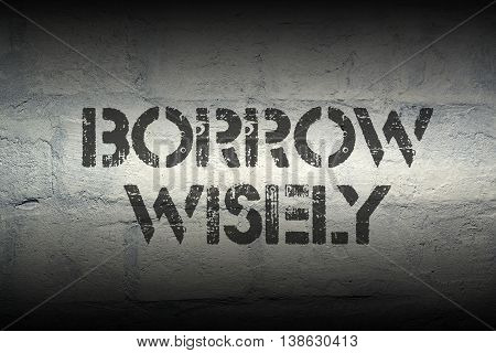 borrow wisely stencil print on the grunge white brick wall