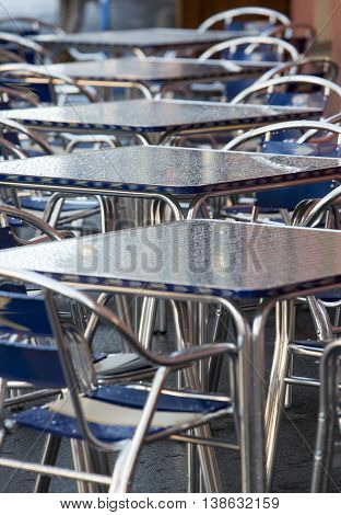 metal tables in a summer cafe and blue chairs
