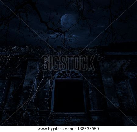 Old ancient window castle with dead tree over moon and cloudy sky Spooky background Halloween concept
