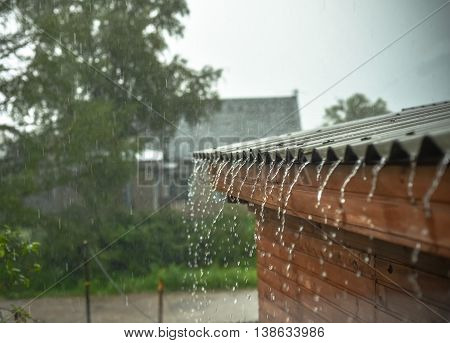 rain flows down from a roof down .