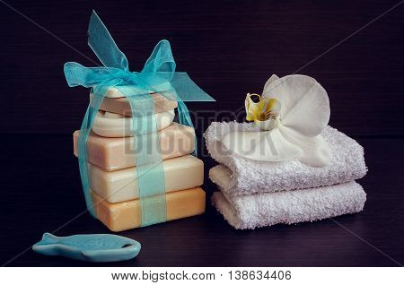Spa setting in purple and blue colors with different kind of natural soaps, soft towels and orchid on dark wooden background. Tower stack of different handmade soaps. Selective focus.