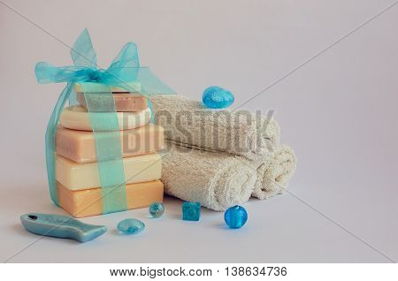 Spa setting with different kind of natural soaps and towels in pastel and blue colors on white background. Bar of natural handmade soap. Tower stack of different soaps on white. Selective focus.