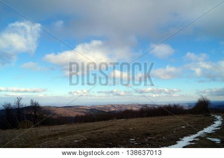 on winter mountain view, accommodation at the foot and a blue sky with white clouds