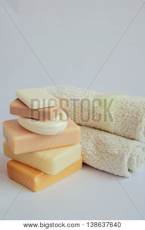Spa setting with different kind of natural soaps and towels in pastel colors on white background. Tower stack of different handmade soaps on white. Selective focus. Place for text. Copy space.