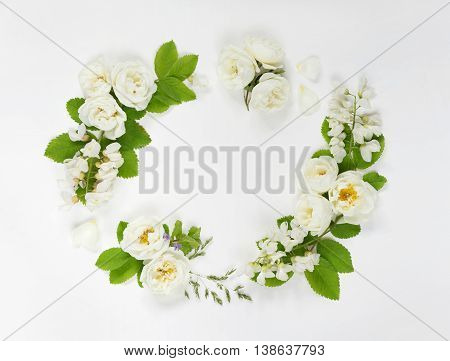 Decorative composition in retro style consisting of white wild rose and white locust flowers with green leaves on white background. Top view flat lay