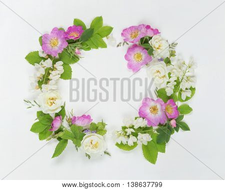 Decorative composition in retro style consisting of pink wild rose and white locust flowers with green leaves on white background. Top view flat lay