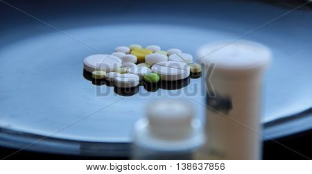 Pills bottle with soft focus over colored tablets on black surface