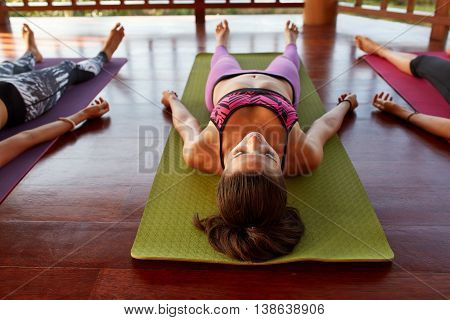Shot of women at yoga class doing savasana lying on exercise mat. Young people relaxing at yoga class.