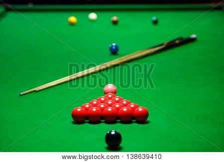 red snooker balls set on a green table, billiards game