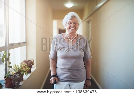 Portrait of happy senior woman with walking stick standing at home. Caucasian female looking at camera and smiling.