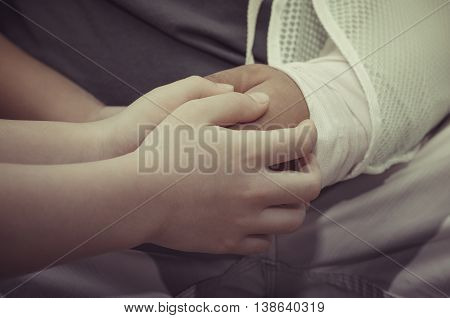 Asian son holding his father's hand who has an accident, vintage filter