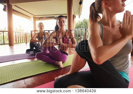 Women Doing Yoga In Twist Pose On Mat