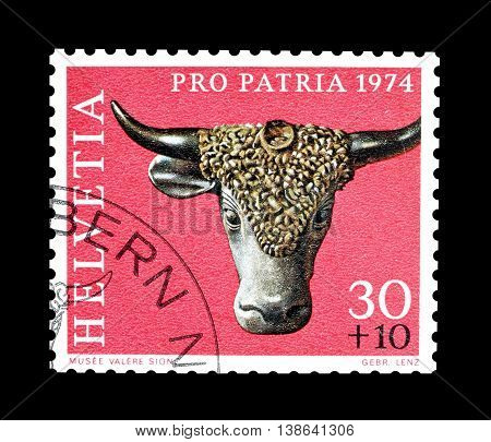 SWITZERLAND - CIRCA 1974 : Cancelled postage stamp printed by Switzerland, that shows Bronze bull head.