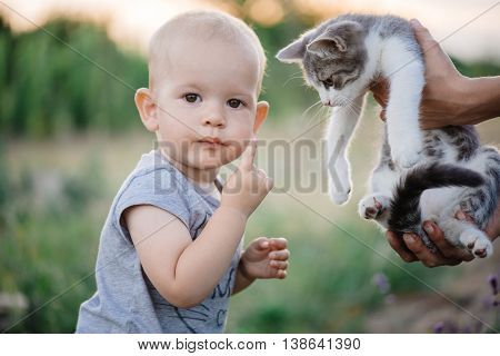 Child playing with cat in garden.