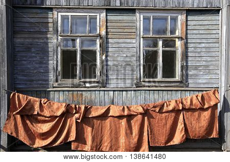 windows with glass in an old wooden house and laundry on the clothesline