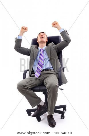 Successful middle aged business man with clenched fist sitting isolated on a chair over white