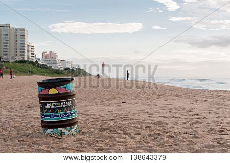 DURBAN SOUTH AFRICA - MARCH 12 2016: Trash can on the beach near fisherman in Umhlanga Rocks