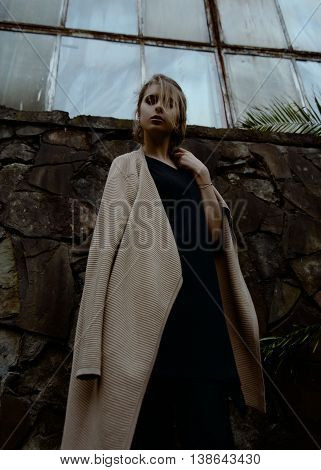 Portrait of a beautiful young blond woman in beige coatand black dress. Industrial background.