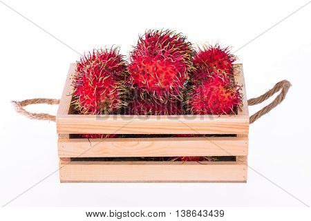 Fresh rambutan in wooden crate on white background.