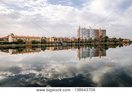 Multi-storey hotel is reflected in the Esperanza lake in Port d'Alcudia. Beautiful reflection of the sky and clouds. Alcudia Mallorca Spain