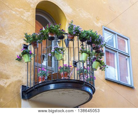 small balcony loggia on the wall of the house with flowers in pots