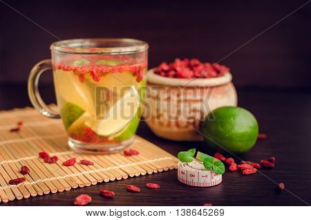 Cup of delicious dietary Goji berry tea with lime on wooden background with measuring tape. Wolfberry for a healthy diet. Alternative medicine. Recovery. Rejuvenation. Slimming. Selective Focus.