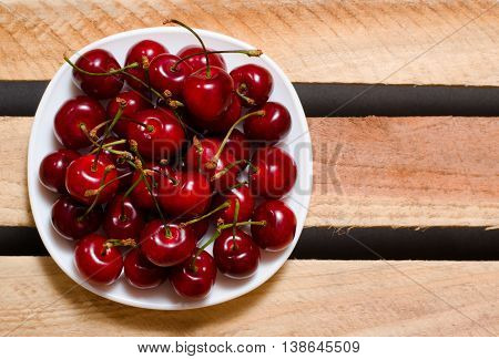 Plate with red cherries on wooden plates top view space for text