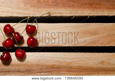 The fruits of sweet cherry on wooden plates, place for text, top view