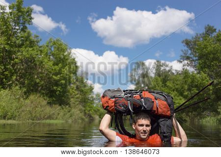 Man in hike crosses the river carrying backpack over his head.