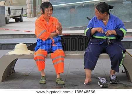 Two Service Workers Are Resting On A Bench Outdoor In Chengdu