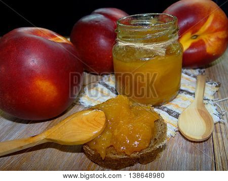 delicious jam made from peaches stands on wooden boards