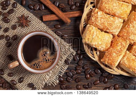 Coffee cup and puff cookies with cheese on old wooden table top view