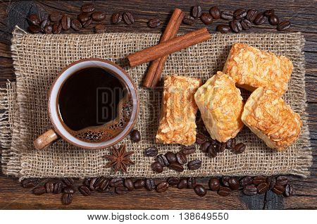 Coffee cup and puff cookies with cheese on rustic wooden table top view