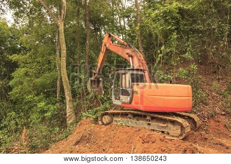 Deforestation environmental problem excavator destroying rainforest trees, Borneo